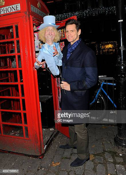 Jim Carrey takes his Dumb and Dumber To Harry Dunne puppet to view the call girl advert cards in a London telephone box after dinner at Zuma...