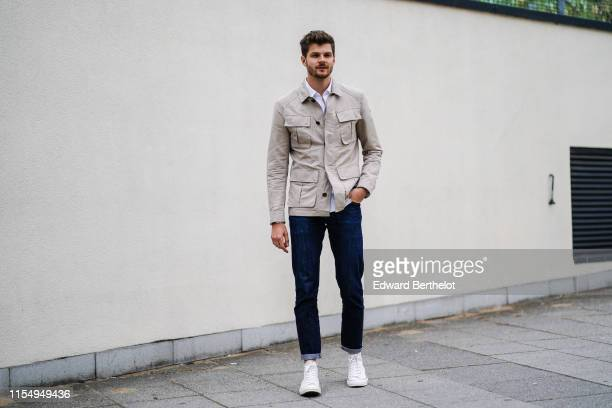 Jim Chapman wears a white jacket blue denim jeans white sneaker shoes a shirt during London Fashion Week Men's June 2019 on June 09 2019 in London...