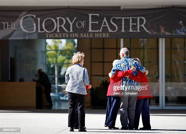 Jim Coleman, President of Crystal Cathedral Ministries, center, hugs ushers Yvette Manson, left, and Betty Spicer, right, who, along with seven...