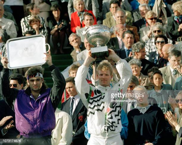 Jim Courier and Andre Agassi of the United States raise their trophies after the 1991 French Open Men's Final on Day 14 at Roland Garros on June 9...