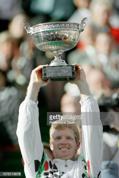 Jim Courier of the United States celebrates with the Coupe des Mousquetaires after winning the men's singles final against Andre Agassi of the United...