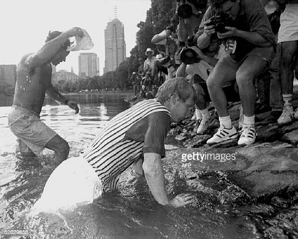 Jim Courier of the US climbs up the bank of the Yarra River 31 January 1993 in Melbourne Courier jumped in the water to cool off after his Australian...