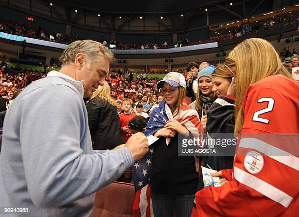 Jim Craig goalie of the 1980 USA Miracle on Ice Olympic gold medalist hockey team signs an USA flag prior to the start of the Men's preliminary Ice...
