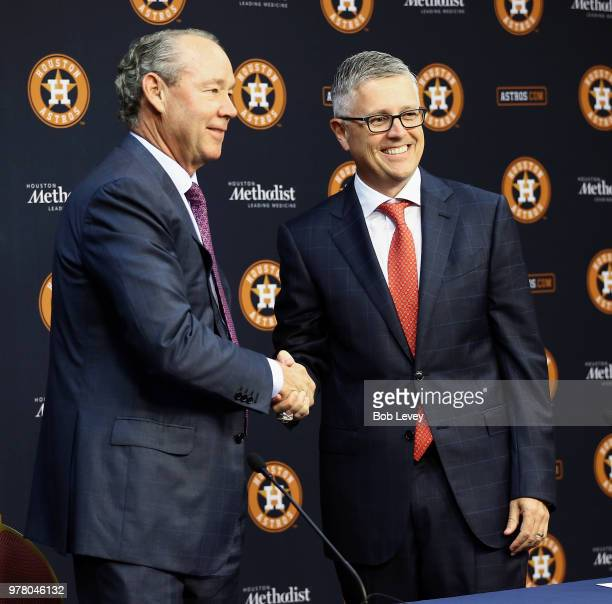 Jim Crane owner and chairman of the Houston Astros left shakes hands with Jeff Luhnow after announcing that Luhnow who has been named President of...