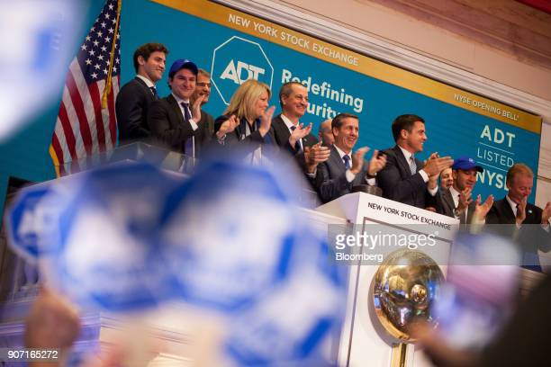 Jim DeVries president of ADT Corp left of center and Timothy Whall chief executive officer of ADT Inc center ring the opening bell during the...