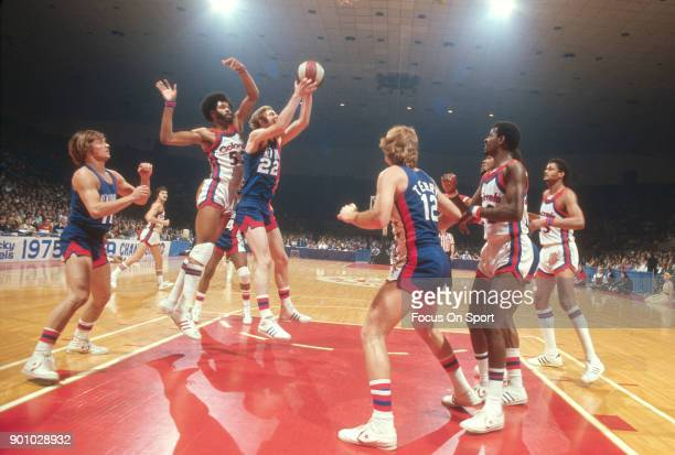 Jim Eakins of the New Jersey Nets grabs a rebound in front of Artis Gilmore of the Kentucky Colonels during an ABA basketball game circa 1976 at...