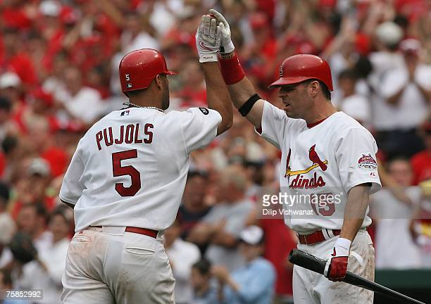 Jim Edmonds of the St Louis Cardinals congratulates teammate Albert Pujols after Pujols knocked in three runs against the Milwaukee Brewers at Busch...