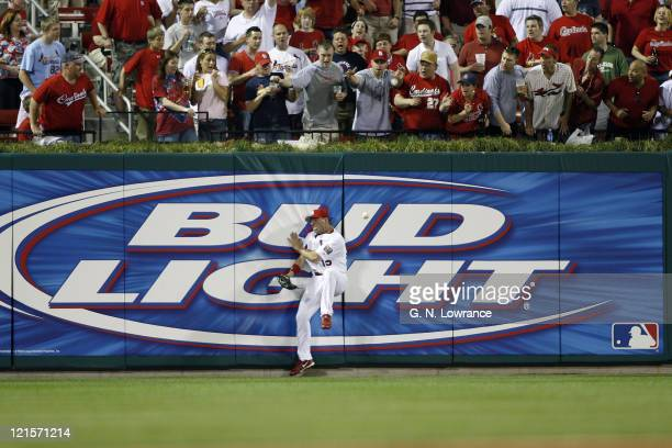 Jim Edmonds of the St Louis Cardinals crashes against the wall during action against the Cincinnati Reds at Busch Stadium in St Louis Missouri on...