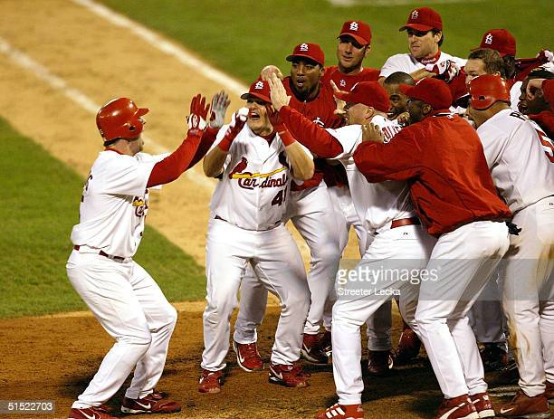 Jim Edmonds of the St. Louis Cardinals reaches home plate and his waiting teammates after hitting a two-run home run in the 12th inning to defeat the...
