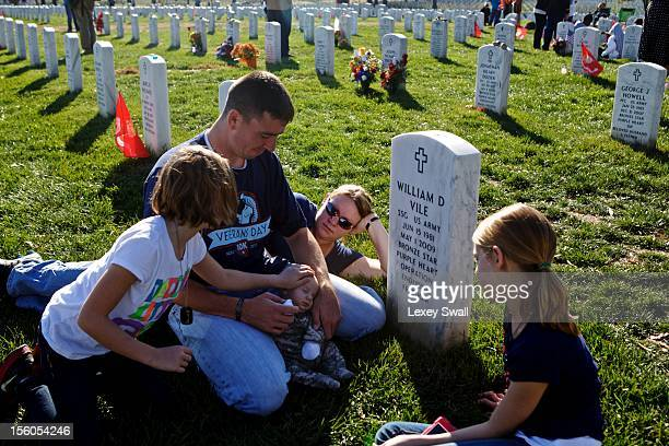 Jim Finnegan his wife Carolyn and their children Colleen Erin and William 2 months sit before the grave of Finnegan's best friend Staff Sgt William...