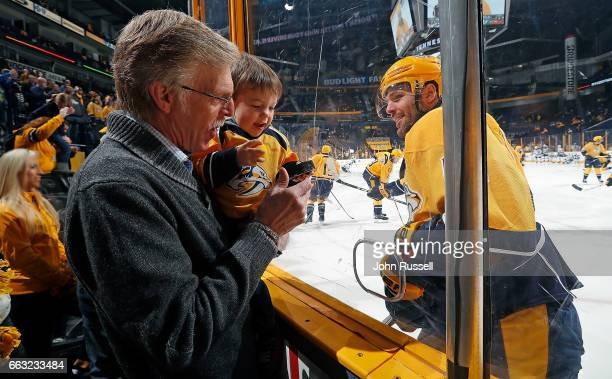 Jim Fisher and his grandson Isaiah get a puck his father Mike Fisher of the Nashville Predators as he skates warmups prior to an NHL game against the...