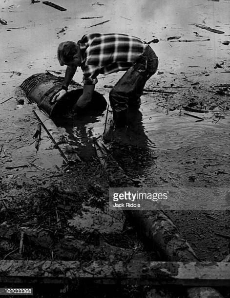 JUN 21 1965 JUN 22 1965 Jim Fuljham an employe of Asphalt Paving Co works to keep a sump pump clear of debris during pumping out of water on the...