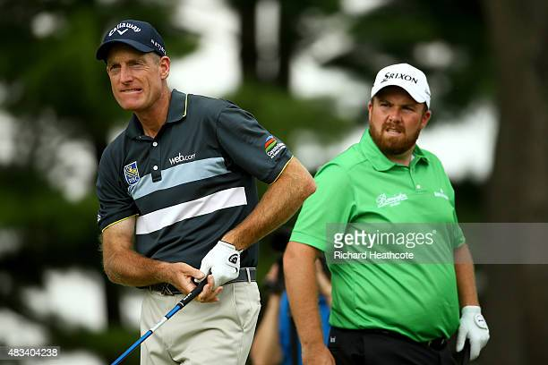 Jim Furyk hits off the fourth tee as Shane Lowry of Ireland looks on during the third round of the World Golf Championships - Bridgestone...