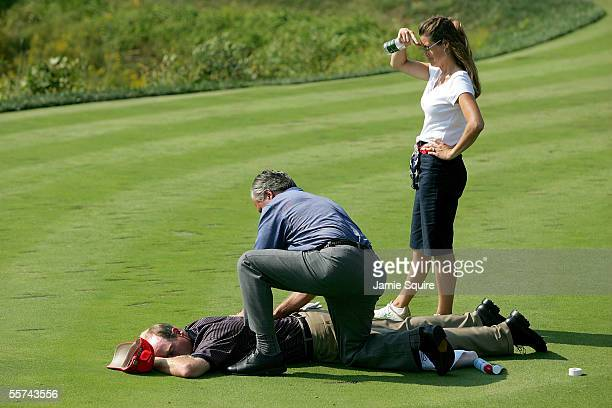Jim Furyk of Team USA suffering from a bad back is attended to by Tom LaFontaine as Furyk's wife Tabitha watches on the 9th hole during Thursday's...