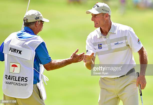Jim Furyk of the United States celebrates with his caddie Mike Fluff Cowan after a shooting a record setting 58 during the final round of the...