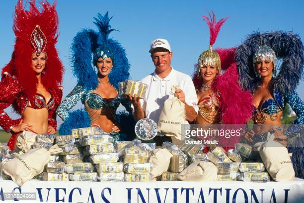 Jim Furyk of the United States celebrates with the trophy $450000 and showgirl performers after winning the PGA Las Vegas Invitational golf...