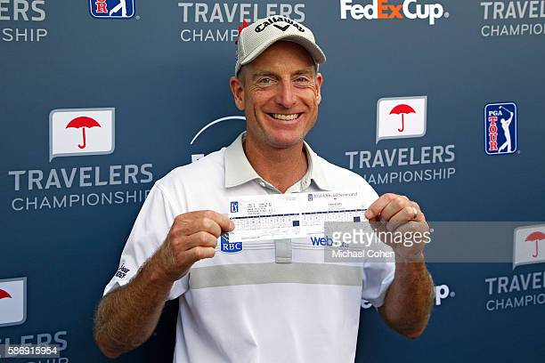 Jim Furyk of the United States poses with his scorecard after shooting a record setting 58 during the final round of the Travelers Championship at...