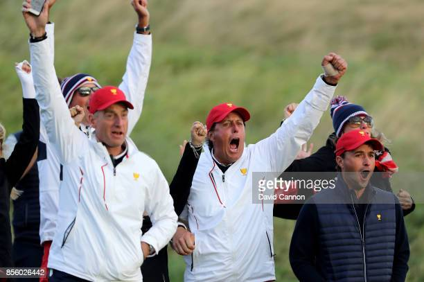 Jim Furyk, Phil Mickelson and Kevin Kisner of the United States team react to Charley Hoffman's chip-in birdie at the 17th hole during the Saturday...