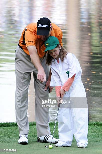 Jim Furyk talks with his daughter Caleigh as she putts during the Par 3 Contest prior to the 2010 Masters Tournament at Augusta National Golf Club on...
