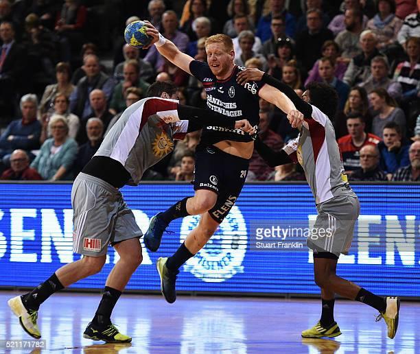 Jim Gottfridsson of Flensburg is challenged by Ramon Tauabo of Luebbecke during the DKB handball Bundeliga match between SG Flensburg Handewitt and...