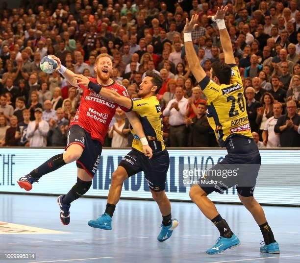 Jim Gottfridsson of SG FlensburgHandewitt is challenged by Alexander Petersson and Ilija Abutovic of RheinNeckar Loewen during the DKB HBL Bundesliga...