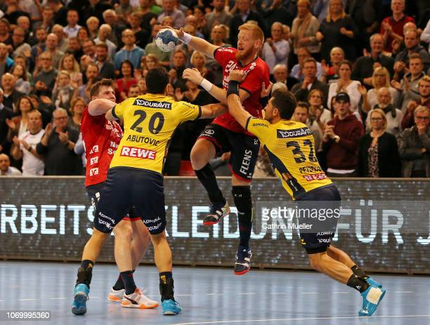 Jim Gottfridsson of SG FlensburgHandewitt is challenged by Ilija Abutovic and Alexander Petersson of RheinNeckar Loewen during the DKB HBL Bundesliga...