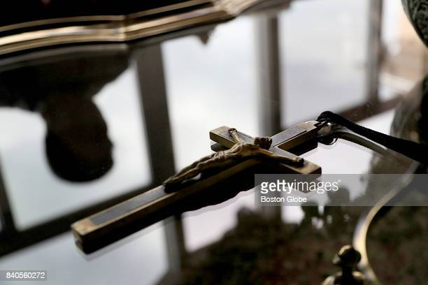 Jim Graham who believes he is the son of a Catholic priest is reflected on in the coffee table with his father's crucifix at his South Carolina home...