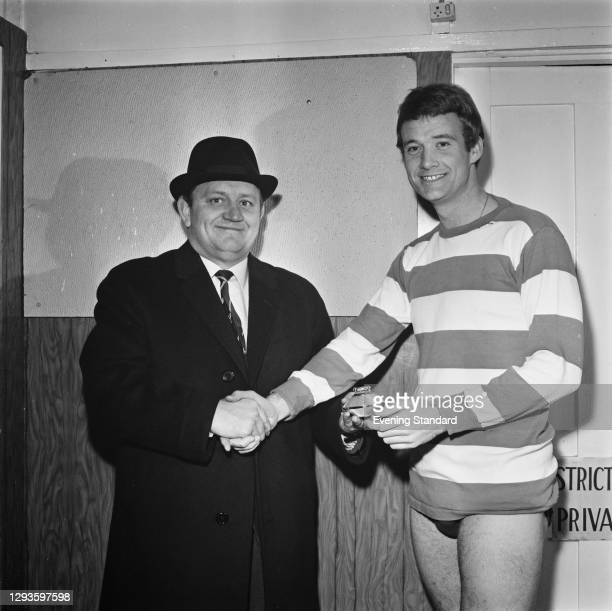 Jim Gregory , chairman of Queens Park Rangers FC, presents a cigarette lighter to footballer Rodney Marsh of QPR, UK, 7th January 1967.