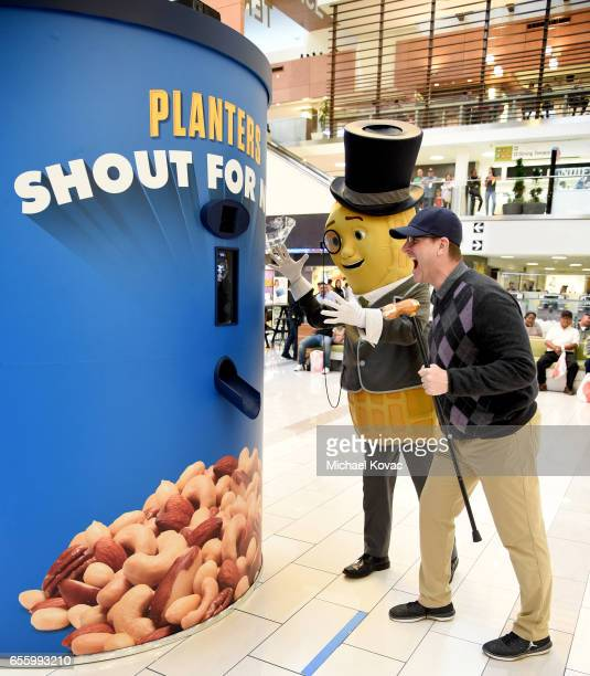 Jim Harbaugh and Mr Peanut interact with shoppers during Planters 'Shout For Nuts' at Westfield Culver City on March 12 2017 in Culver City California