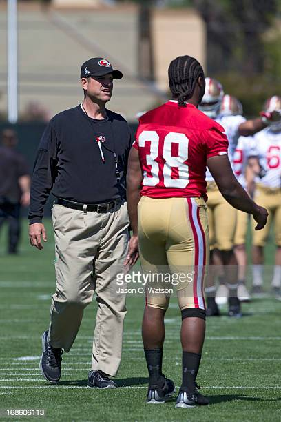 Jim Harbaugh head coach of the San Francisco 49ers walks next to Marcus Lattimore during the San Francisco 49ers rookie minicamp at their training...