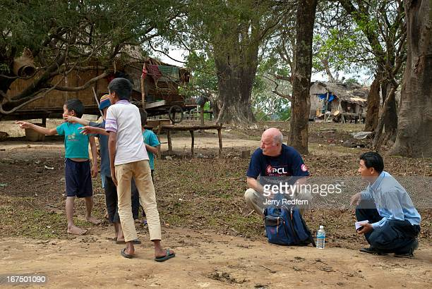 Jim Harris of Phoenix Clearance LTD center and his coworker Bounphasit Xayavong right talk with local kids who found a pair of phosphorous bombs near...