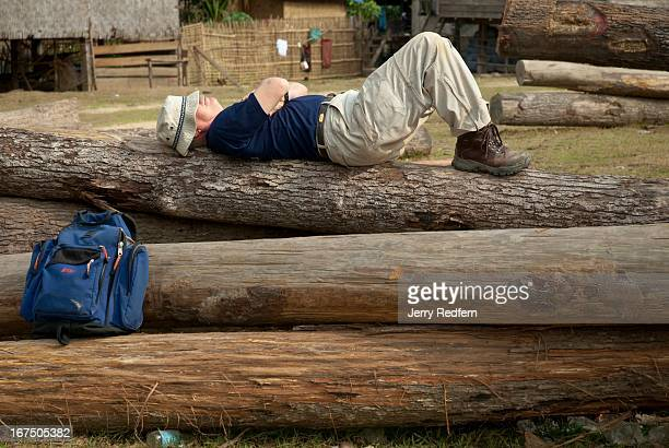 Jim Harris of Phoenix Clearance LTD takes a nap atop a pile of logs cleared to make way for the reservoir behind the Nam Theun 2 dam He had spent...