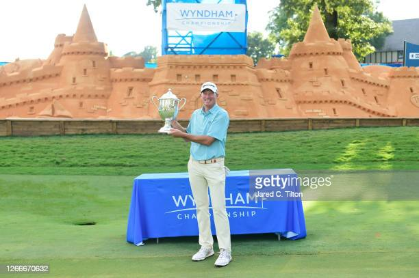 Jim Herman of the United States celebrates with the trophy on the 18th green after winning during the final round of the Wyndham Championship at...