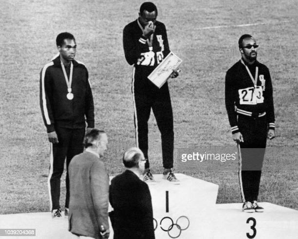 Jim Hines of the USA Lennox Miller of Jamaica and Charles Greene of the USA stand on the podium 14 October 1968 after receiving their medals for the...