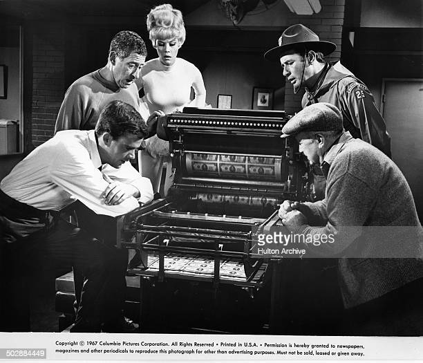 Jim Hutton Jack Gilford Dorothy Provine Joey Bishop and Walter Brennan watch the paper press print money in a scene from the Columbia Pictures...