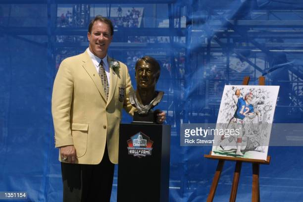 Jim Kelly stands next to his bust and artwork after his induction into the National Football League Hall of Fame on August 3, 2002 at Fawcett Stadium...
