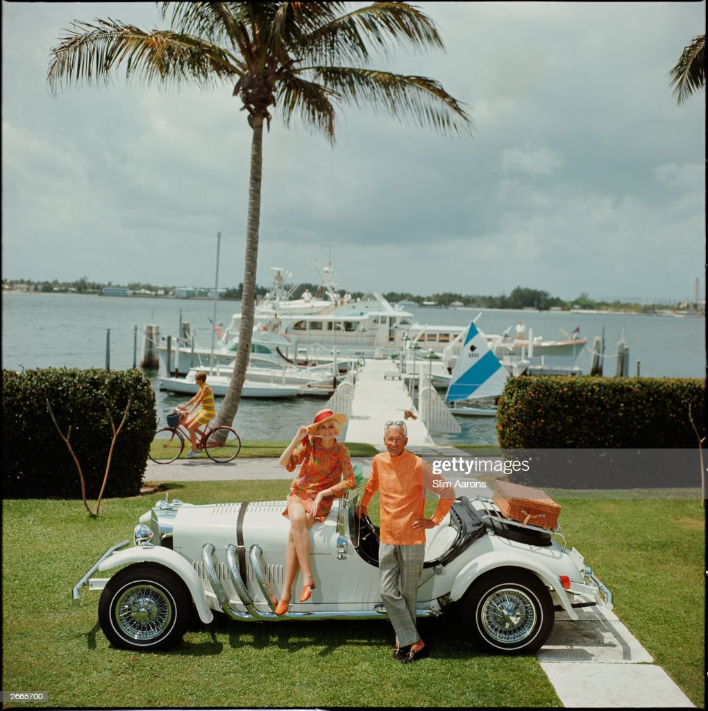 Jim Kimberly and his wife, with his white sports car and white boats moored on Lake Worth. A Palm Beach socialite, he acts as Honorary Consul of Jordan. Original Artwork: A Wonderful Time - Slim Aarons