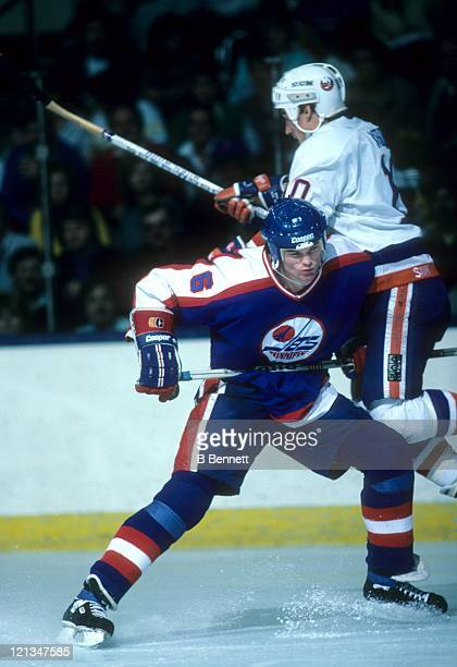 Jim Kyte of the Winnipeg Jets checks Alan Kerr of the New York Islanders during their game on November 1 1986 at the Nassau Coliseum in Uniondale New...