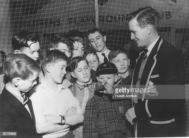 Jim Laker England and Surrey cricketer showing schoolboy fans how to hold a cricket ball