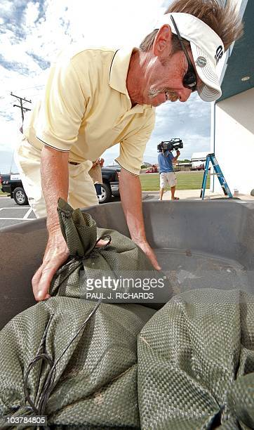 Jim Lassiter, Manager of the Kitty Hawk Mattress Discounters, does some heavy lifting and grabs a sandbag to secure his store as Hurricane Earl...