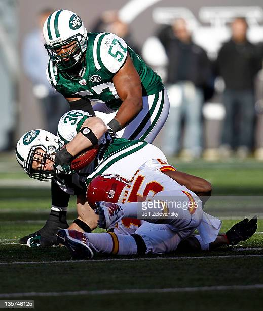 Jim Leonhard of the New York Jets is tackled by Steve Breaston of the Kansas City Chiefs in front of Bart Scott of the New York Jets during their...