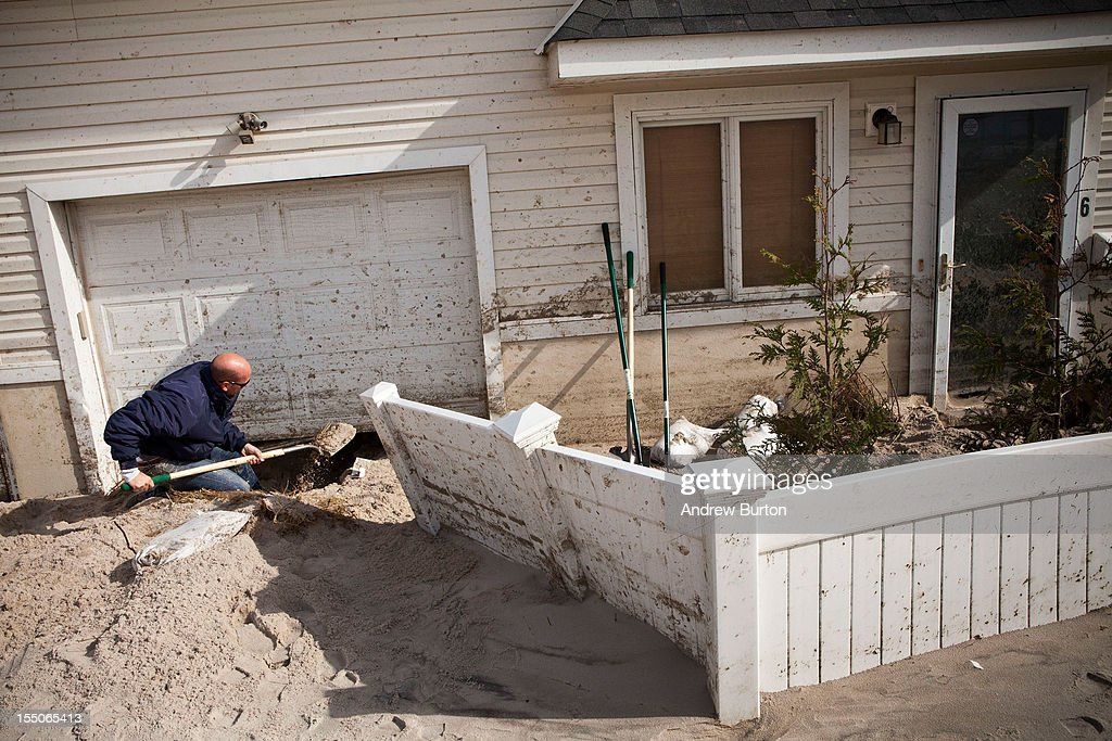 Jim Margiotta digs sand out from under his garage door, which was caused by Hurricane Sandy, on October 31, 2012 in Long Beach, New York.The storm has claimed many lives in the United States and has caused massive flooding across much of the Atlantic seaboard. U.S. President Barack Obama has declared the situation a 'major disaster' for large areas of the U.S. east coast, including New York City, with widespread power outages and significant flooding in parts of the city.
