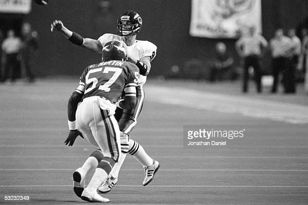 Jim McMahon of the Chicago Bears throws a pass under pressure from Chris Martin of the Minnesota Vikings during the game at the Metrodome on...