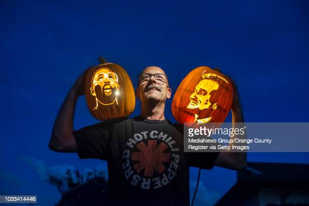 Jim Morey of Huntington Beach who refers to himself as a professional pumpkin carver shows off two of his carvings of former Laker basketball player...