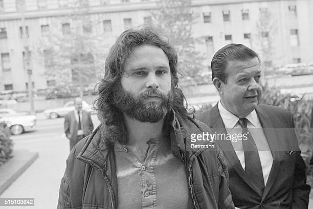 Jim Morrison lead singer of the rock group 'The Doors' is accompanied by his attorney Max Fink as he arrives at the Los Angeles Federal Building to...