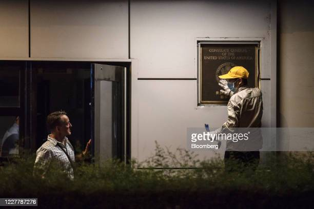 Jim Mullinax, U.S. Consul General in Chengdu, left, speaks with a worker trying to remove a plaque from the front of the U.S. Consulate General...