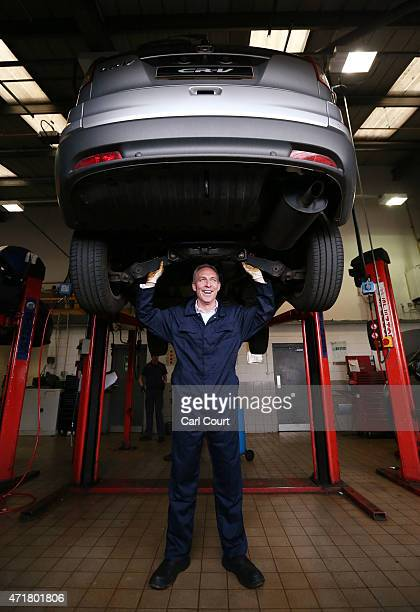 Jim Murphy the leader of the Scottish Labour Party poses for a photograph under a car during a visit to a Honda dealership on May 1 2015 in Paisley...