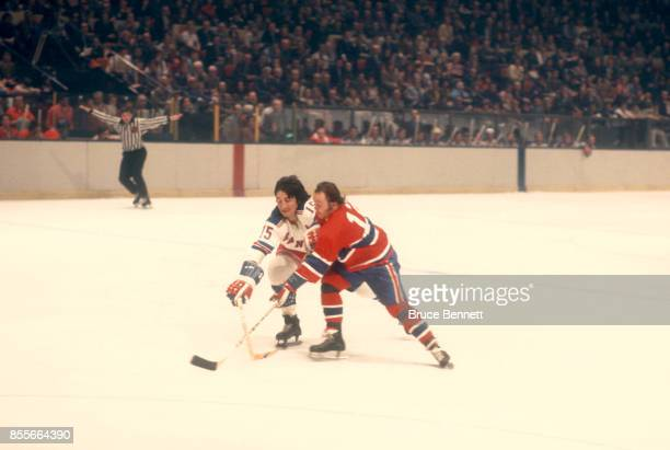 Jim Neilson of the New York Rangers tries to poke check the puck away from Yvan Cournoyer of the Montreal Canadiens during an NHL game circa 1974 at...