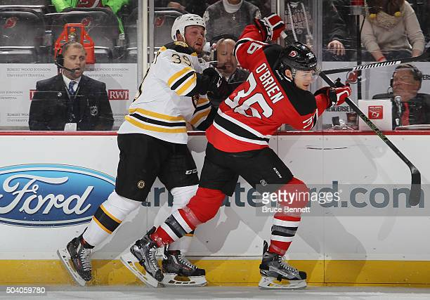 Jim O'Brien of the New Jersey Devils checks Matt Beleskey of the Boston Bruins during the first period at the Prudential Center on January 8 2016 in...