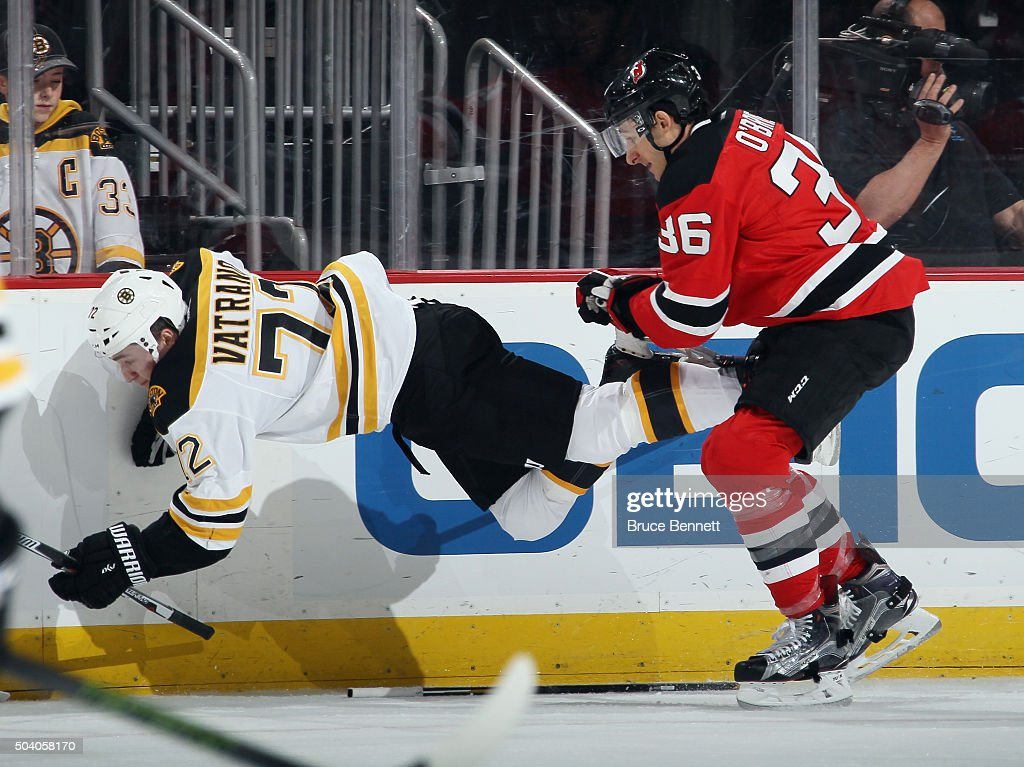 Jim O'Brien #36 of the New Jersey Devils hits Frank Vatrano #72 of the Boston Bruins during the first period at the Prudential Center on January 8, 2016 in Newark, New Jersey.